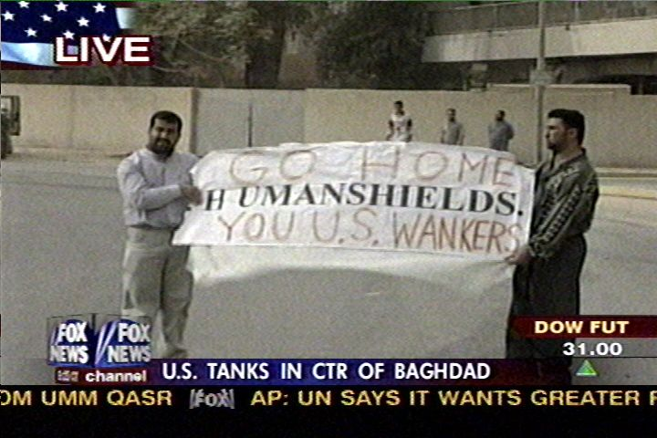 "Two iraqis hold up a banner that has ""H UMANSHIELDS."" printed in the middle, with the words ""GO HOME"" written above, and ""YOU U.S. WANKERS"" written underneath."
