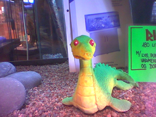 A green and yellow dinosaur with red eyes.