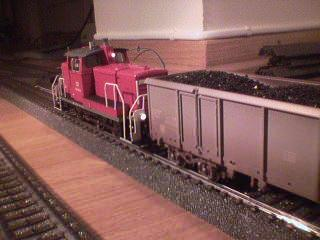 A short but still very detailed red locomotive coupled to the same coal truck.